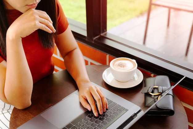 Mulher com as mãos digitando no teclado do laptop. mulher que trabalha no escritório com café