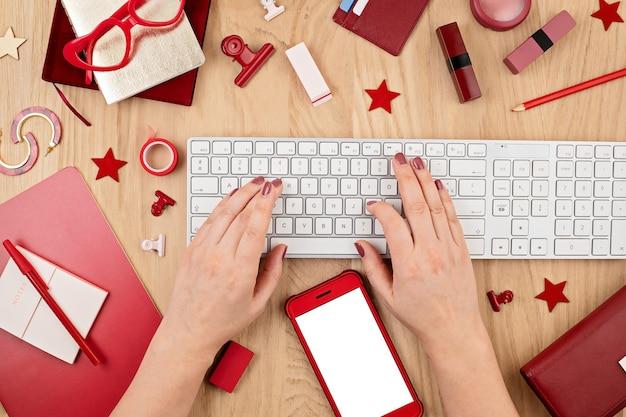 Mulher com as mãos digitando no teclado. vista de cima, configuração plana. compras online, redes sociais, navegação na internet, conceito de blog online