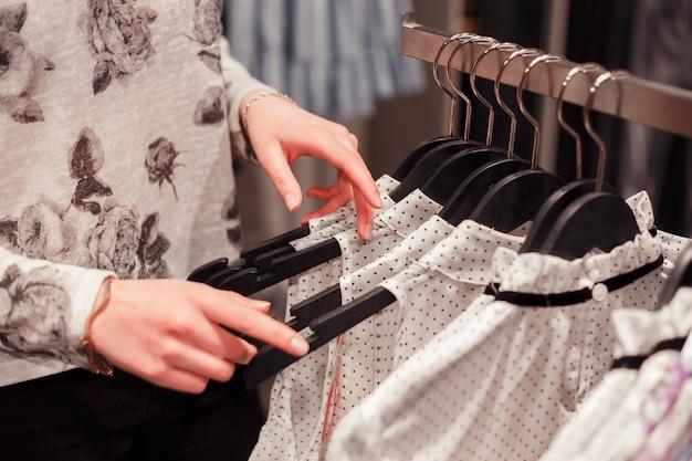 Mulher com as mãos em cabides em uma loja para comprar roupas