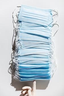 Mulher com as mãos em luvas de látex segurando uma pilha de máscaras médicas faciais