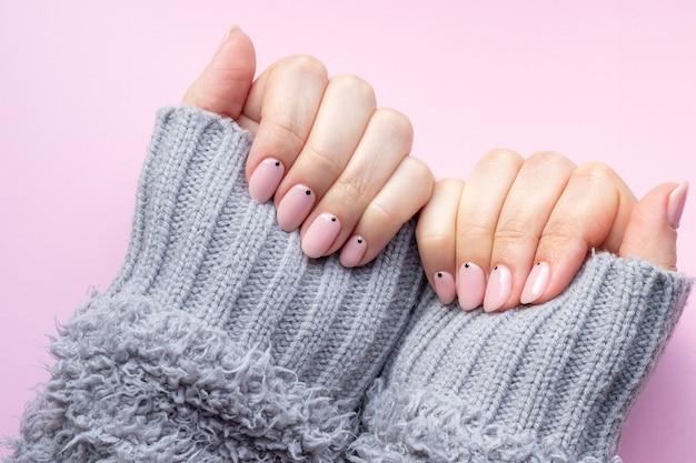 Mulher com as mãos em luvas de malha com unhas rosa nude