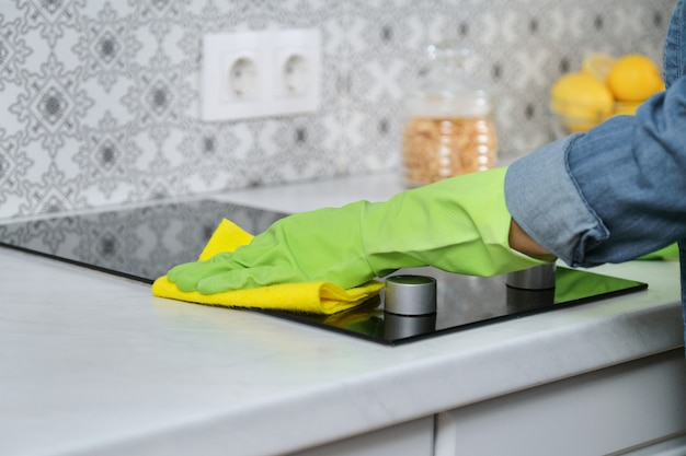 Mulher com as mãos em luvas, lavar e limpar o fogão elétrico na cozinha