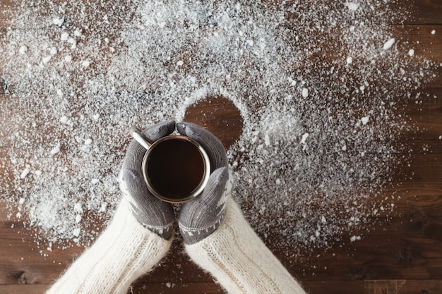 Mulher com as mãos em luvas segurando uma caneca de café na neve