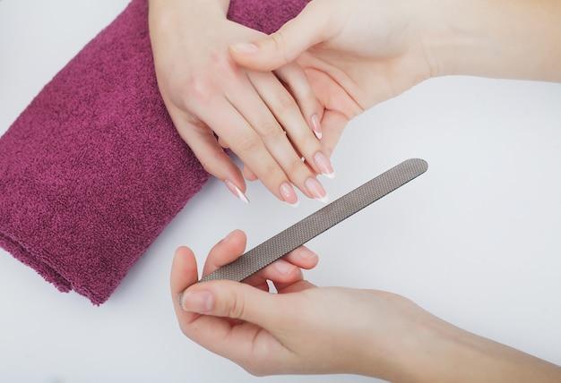 Mulher com as mãos em um salão de beleza, recebendo um procedimento de manicure. manicure spa.