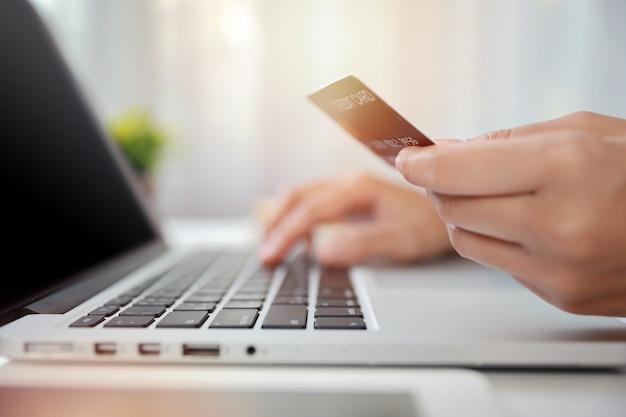 Mulher com as mãos em um terno preto sentado e segurando o cartão de crédito e usando o computador portátil na mesa para pagamento online ou compras online. mulher de negócios usando a internet enquanto trabalhava. conceito de e-banking