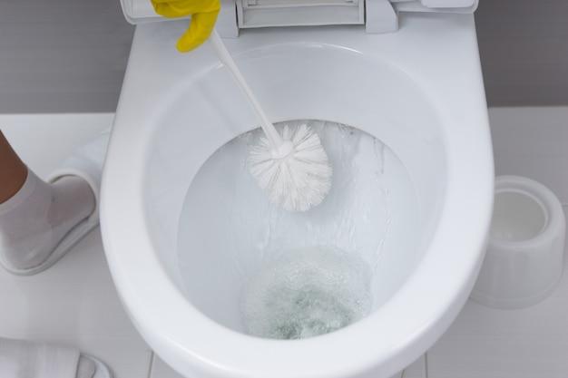 Mulher com as mãos enluvadas esfregando um vaso sanitário com uma escova e sabonete germicida enquanto dá descarga na cisterna