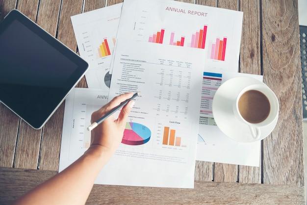 Mulher com as mãos escrevendo um gráfico de documento financeiro de negócios na mesa do escritório com uma xícara de café