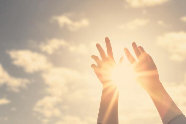 Mulher com as mãos estendidas para o céu e o sol