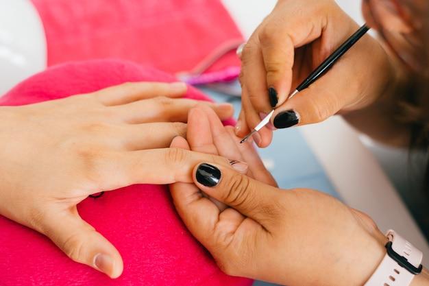 Mulher com as mãos fazendo manicure no salão.