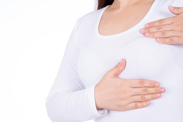 Mulher com as mãos fazendo o autoexame das mamas para verificar nódulos e sinais de câncer de mama.
