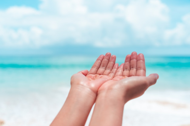Mulher com as mãos juntas como orando em frente a praia limpa natureza e céu azul.