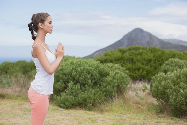 Mulher com as mãos juntas de pé na paisagem do campo
