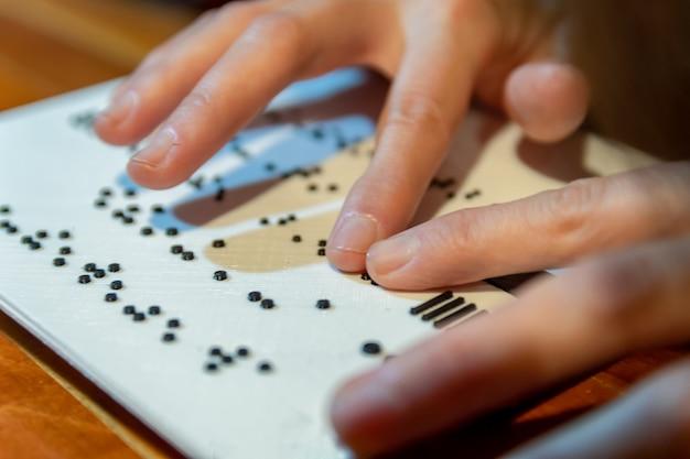 Mulher com as mãos lendo texto em braille