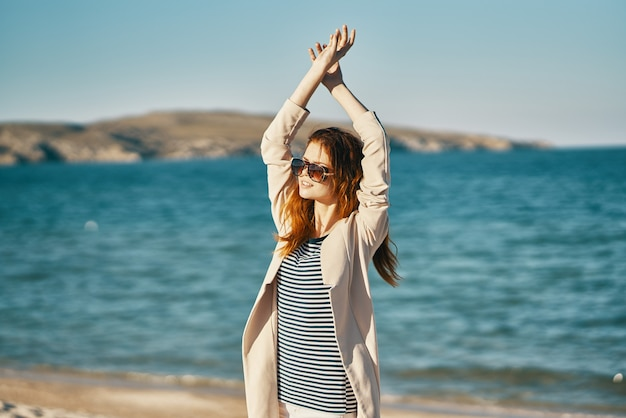 Mulher com as mãos levantadas na praia, ondas, montanhas, ar fresco