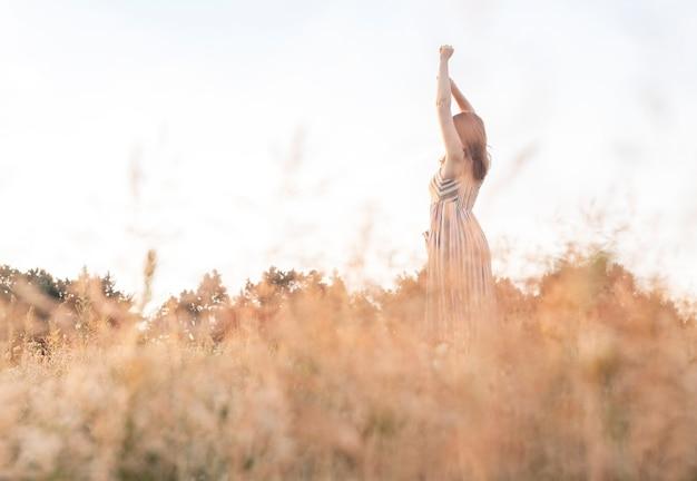 Mulher com as mãos levantadas no campo de verão, desfrutando da liberdade e do prazer da paisagem de ser livre ...