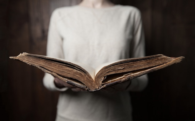 Mulher com as mãos na bíblia. ela está lendo e orando pela bíblia em um espaço escuro sobre uma mesa de madeira