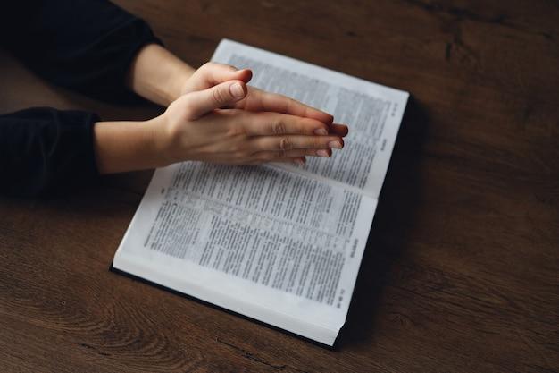 Mulher com as mãos na bíblia. ela está lendo e orando pela bíblia em um espaço escuro sobre uma mesa de madeira.