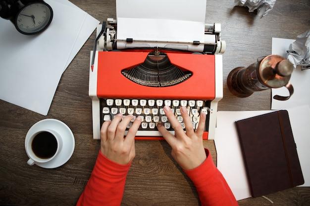Mulher com as mãos na máquina de escrever vintage vermelha com papel em branco na mesa de madeira