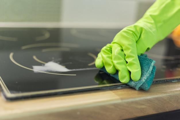 Mulher com as mãos nas luvas limpa a placa de cerâmica elétrica da cozinha com uma esponja e detergente