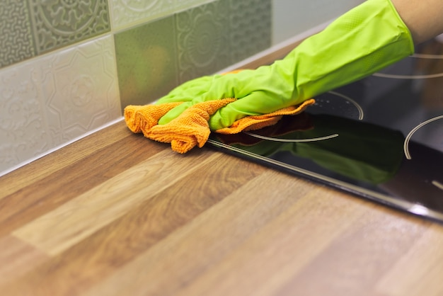 Mulher com as mãos nas luvas limpando fogão elétrico de cozinha, polindo vidro com pano de microfibra