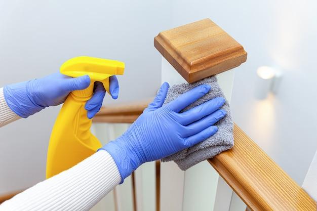 Mulher com as mãos nas luvas limpando o corrimão da escada com pano