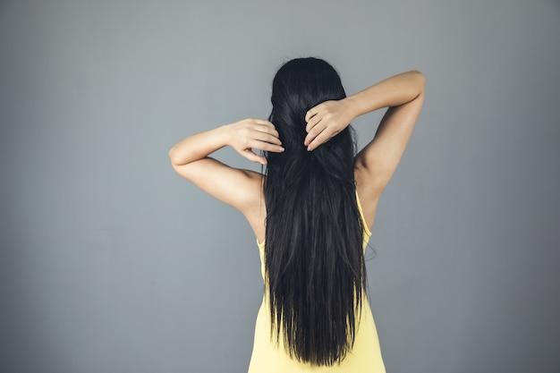Mulher com as mãos no cabelo grisalho