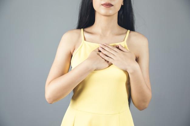 Mulher com as mãos no coração cinza