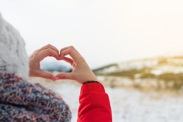 Mulher com as mãos no inverno símbolo em forma de coração de sentimentos e conceito de estilo de vida com a luz do sol da natureza ao fundo. com cópia espaço dia dos namorados. ame.
