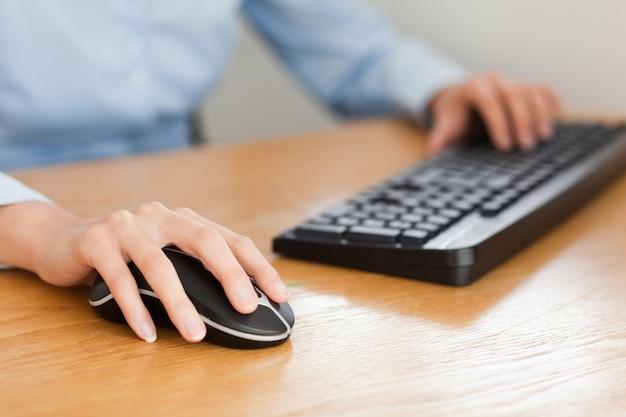 Mulher com as mãos no mouse e no teclado