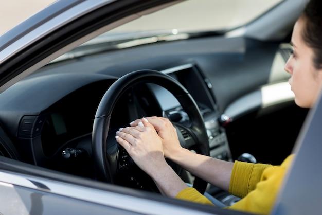 Mulher com as mãos no volante