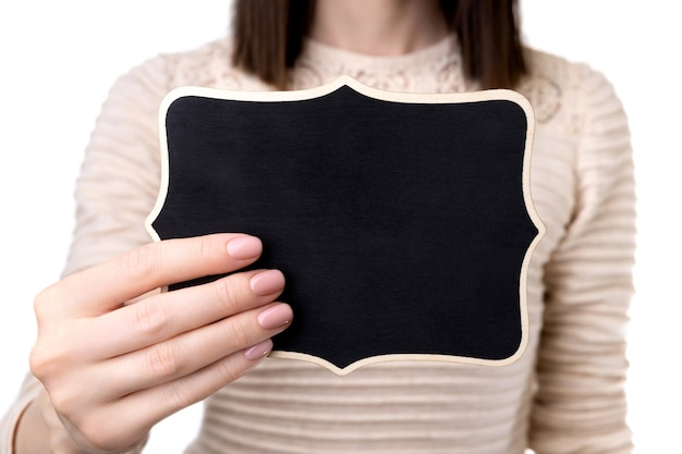 Mulher com as mãos preparadas com design de unhas rosa bege nude, segurando uma placa de madeira. modelo de escritório comercial