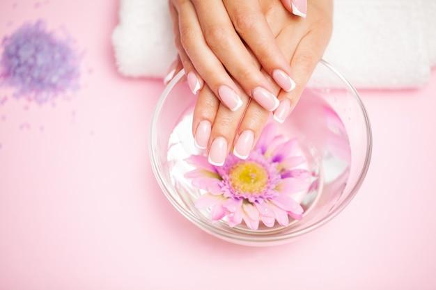 Mulher com as mãos recebendo uma manicure no salão de beleza.