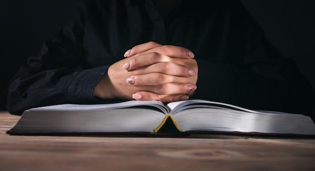 Mulher com as mãos rezando com a bíblia no quarto escuro