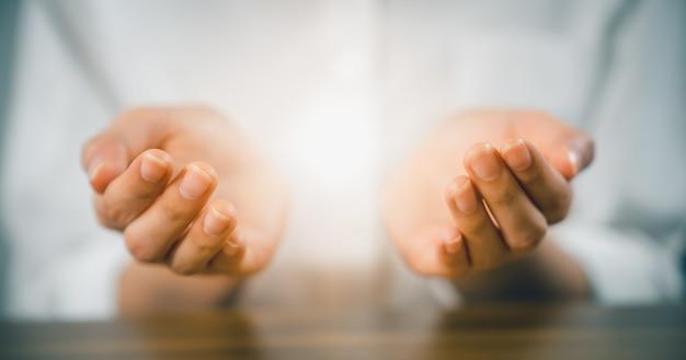 Mulher com as mãos rezando (faz um dua) e luz na palma da mão.