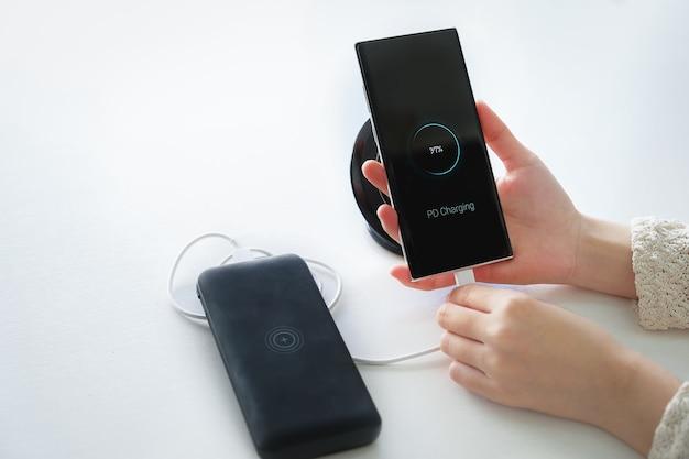 Mulher com as mãos segurando a bateria de carregamento de smartphone de banco de energia externo com o uso de tecnologia de carregamento pd