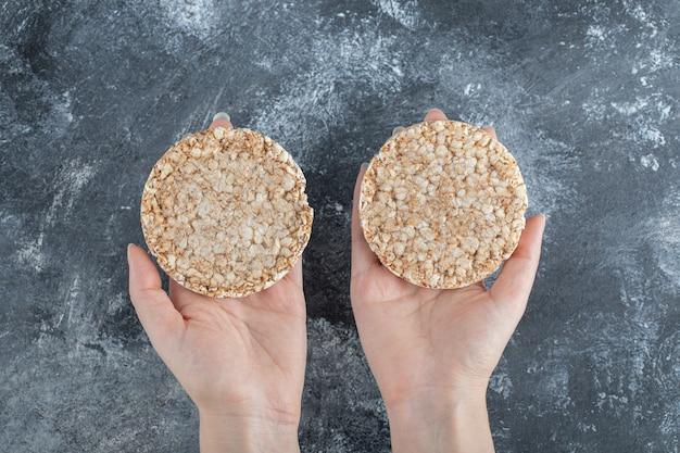 Mulher com as mãos segurando dois deliciosos bolos de arroz.