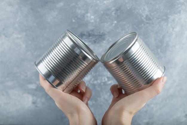 Mulher com as mãos segurando duas latas metálicas em mármore.