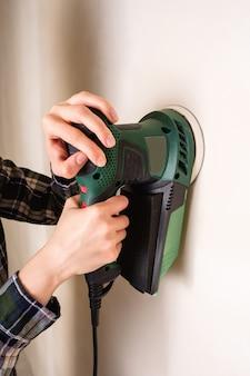 Mulher com as mãos segurando e trabalhando com lixadeira elétrica para alisar a superfície da parede de gesso, conceito de renovação de sala