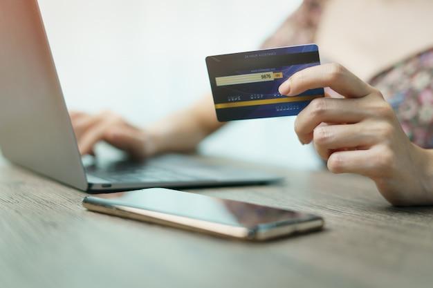 Mulher com as mãos segurando e usando cartão de crédito para compras on-line.