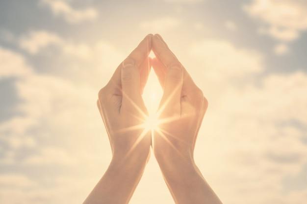 Mulher com as mãos segurando o sol ao amanhecer