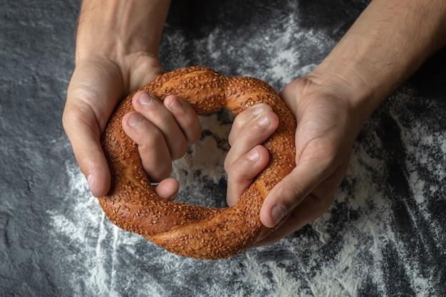 Mulher com as mãos segurando simit turco fresco.