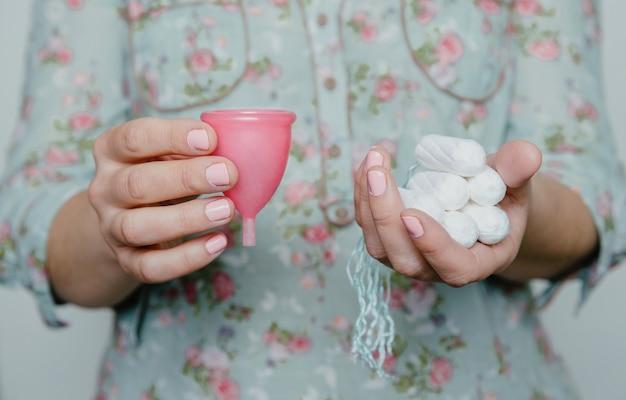 Mulher com as mãos segurando tampões e copo menstrual. comparação de diferentes métodos de higiene íntima feminina.