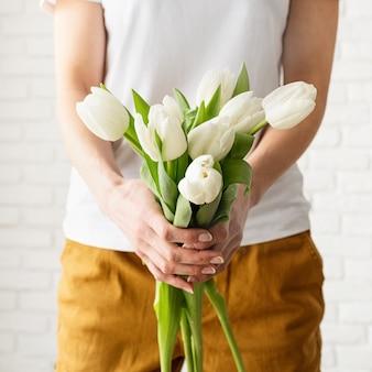 Mulher com as mãos segurando um buquê de tulipas brancas