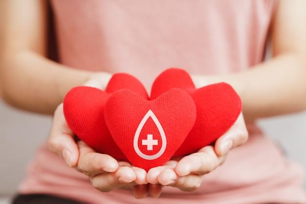 Mulher com as mãos segurando um coração vermelho com sinal de doador de sangue. conceito de saúde, medicina e doação de sangue