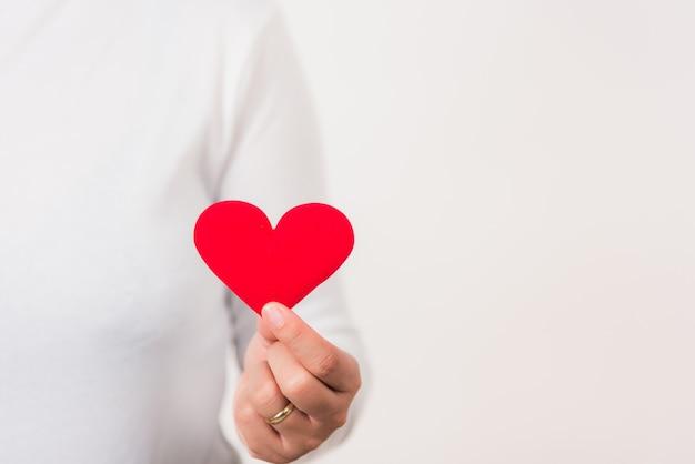 Mulher com as mãos segurando um coração vermelho para ajudar doação de assistência médica