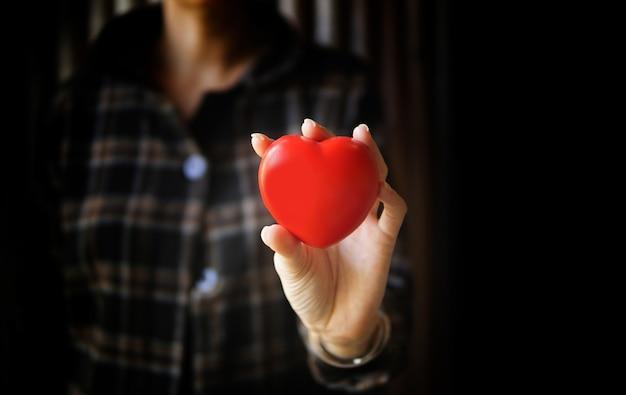 Mulher com as mãos segurando um coração vermelho.