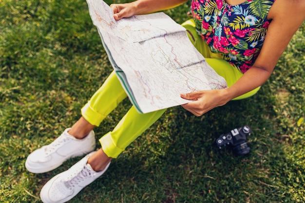 Mulher com as mãos segurando um mapa, viajante com câmera se divertindo no estilo da moda de verão no parque, roupa colorida hipster, sentado na grama, calças amarelas