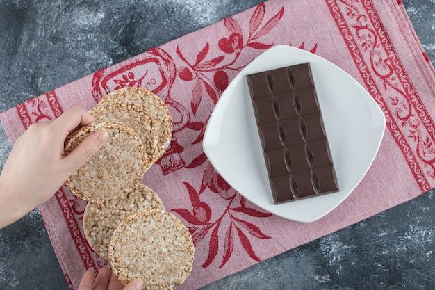 Mulher com as mãos segurando um pão de arroz crocante com barra de chocolate.