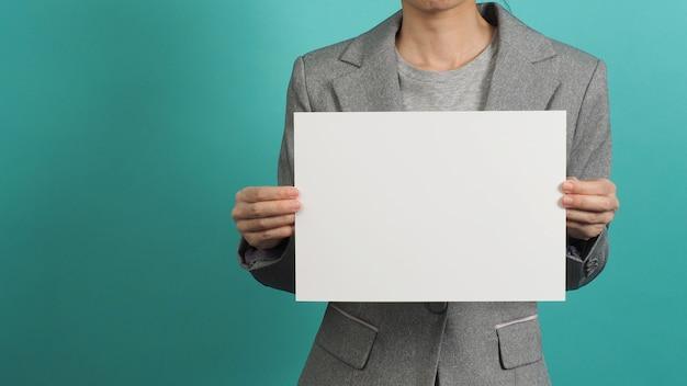 Mulher com as mãos segurando um papel em branco e vestir um terno cinza isolado sobre fundo azul e verde.
