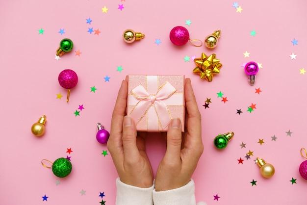 Mulher com as mãos segurando um presente decorado com fita em fundo rosa com bolas de natal e multicolo.